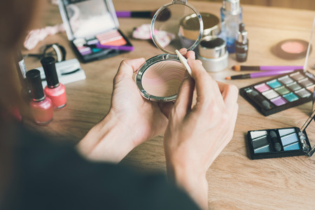 dressing table: Girl doing makeup on dressing table with cosmetics