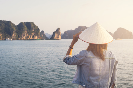Woman traveler with Non La (Vietnam hat) looking beautiful natural view at Halong bay in Vietnam