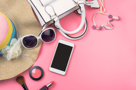 Woman handbag with makeup, cellphone and accessories isolated on pink background, Fashion concept