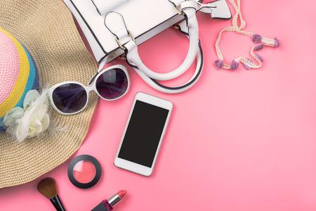 Vrouw handtas met make-up, mobiele telefoon en accessoires geïsoleerd op roze achtergrond, Fashion concept Stockfoto - 74861752