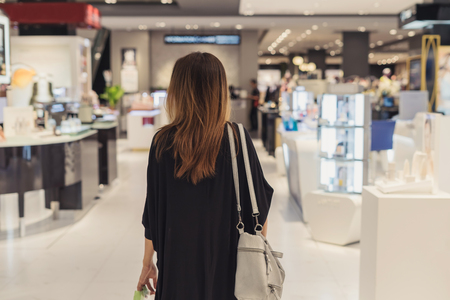 Young asian woman walking in cosmetics department at the mall