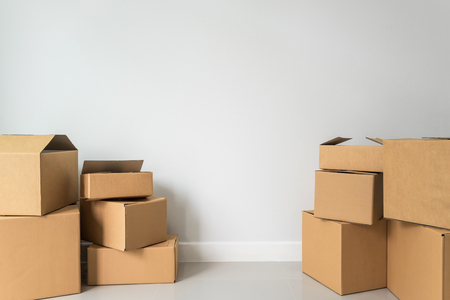 Pila di scatole di cartone nella stanza vuota nella nuova casa con lo spazio della copia Archivio Fotografico