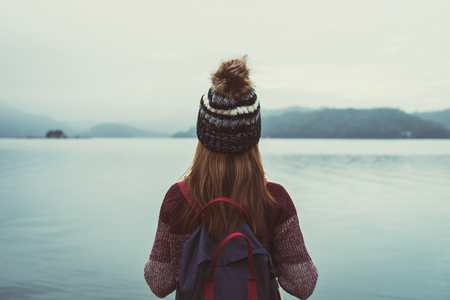 孤独な女性旅行者は、気にせず、川を見て立っている
