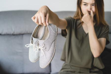 Junge asiatische Frau, die zu Hause ein Paar stinkende und stinkende Schuhe hält