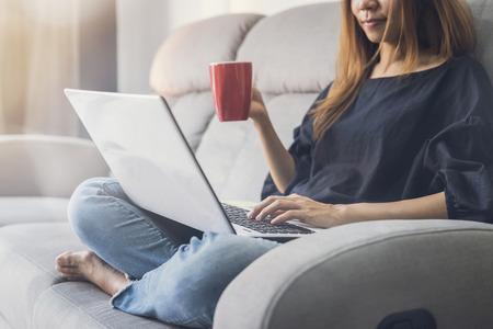 노트북을 사용 하 고 집에서 소파에 cofee 마시는 젊은 여자 스톡 콘텐츠