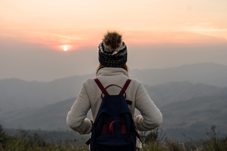 Young woman traveler looking at sunrise over the mountain