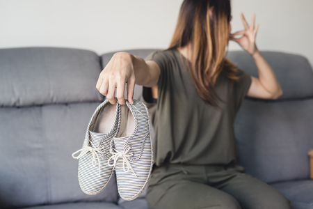 Young asian woman holding a pair of smelly and stinky shoes at home