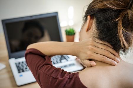Młoda kobieta pracuje w domu i ma ból szyi, zespół opieki zdrowotnej i koncepcja biura problemu Zdjęcie Seryjne