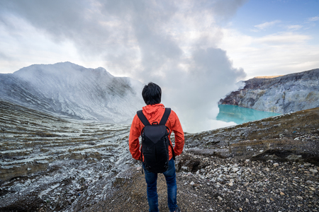 Young travler looking at Sulfur burned by blue flame in the crater blue lake at Kawah Ijen, Indonesia Stock Photo
