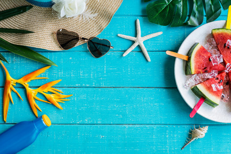 Women's casual clothes with accessories items and tropical fruits and flowers on white wooden background, Summer concept