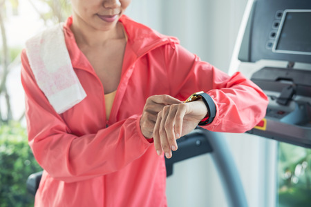 Young sport woman using smart watch on treadmill in gym, Fitness, training lifestyle concept Фото со стока
