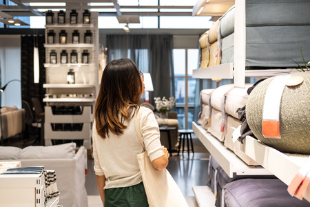 Young woman choosing furniture in a modern home furnishings store Reklamní fotografie