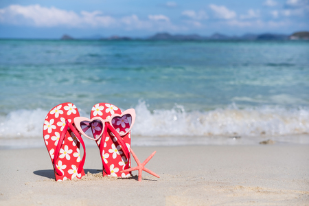 Flip flops and sunglasses on white sandy tropical beach, Summer vacation and travel concept 版權商用圖片
