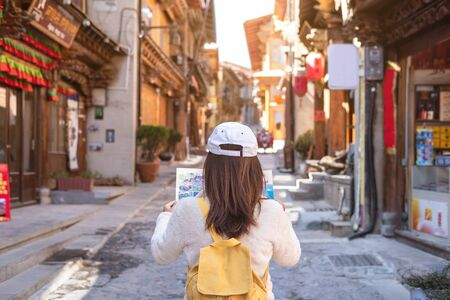 Young woman traveler walking in the old town, Shangri-la and looking the map, Travel concept Imagens