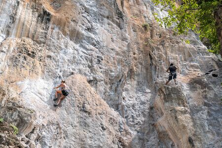 Mountain climber on climbing Route using rope at railay beach in Krabi, Thailand