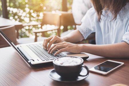 Junge Frau mit Smartphone und Laptop mit Tasse Kaffee im Café