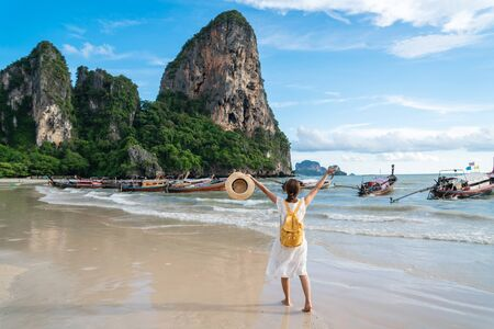 Young woman traveler enjoying a summer vacation at tropical sand beach in Krabi, Thailand