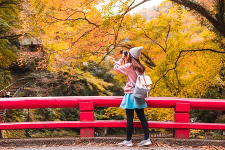 Young woman traveler looking and photographing beautiful autumn in Japan, Travel lifestyle concept Stock Photo