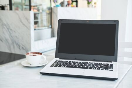 Laptop computer with cup of coffee in cafe 写真素材