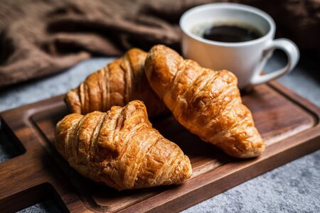 Breakfast with fresh croissants and cup of black coffee on wooden board