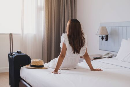 Young asian woman traveler with luggage sitting and relaxing on the bed in hotel room Stock Photo