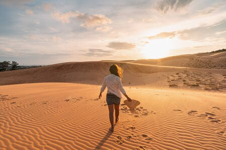 Young woman traveler looking sunset at red sand dunes in Vietnam, Travel lifestyle concept Stockfoto