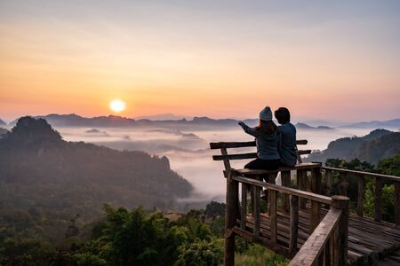 Young couple traveler looking at sea of mist and sunset over the mountain at Mae Hong Son, Thailand Banque d'images
