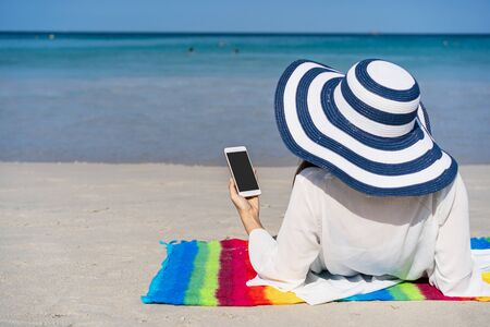 Young asian woman traveler using her smartphone at tropical sand beach, Summer vacation concept Standard-Bild