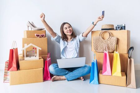 Happy young asian woman with colorful shopping bag, fashion items and stack of cardboard boxes at home, Using credit card for online shopping concept Stock fotó