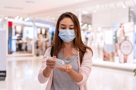 Young asian woman wearing surgical mask and using alcohol gel to avoid infections corona virus and bacteria at the mall, New normal and lifestyle concept