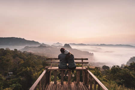 Young couple traveler looking at sea of mist and sunset over the mountain at Mae Hong Son, Thailand Imagens