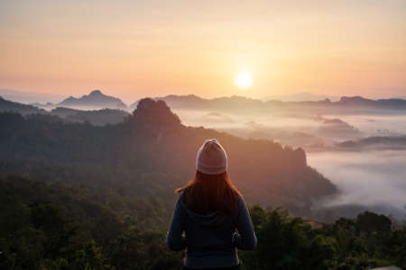 Young woman traveler looking at sea of mist and sunset over the mountain Imagens