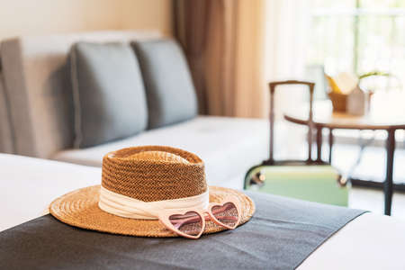 Hat and sunglasses with luggage in hotel room, Travel concept Imagens
