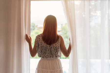 young woman opening curtains in the morning and looking through the window