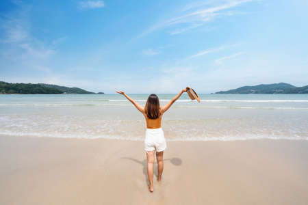 Young woman traveler relaxing and enjoying at beautiful tropical white sand beach with wave foam and transparent sea, Summer vacation and Travel concept Standard-Bild