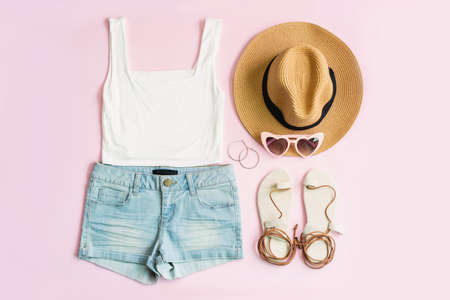 Fashion summer women's clothes set with accessories on pink background, Flat lay, Top view