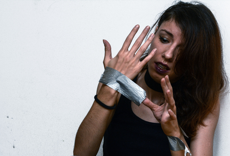 A woman trying to get the duct tape off her as a concept of an abuse Zdjęcie Seryjne