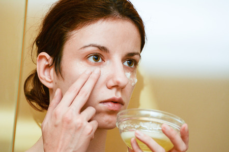 Redhead model using albumen or egg white to relieve the dark circles under her tired, puffy eyes
