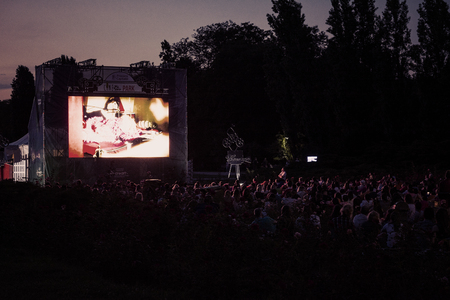02 August 2018-Bucharest, Romania. People waiting and watching in the public park Herastrau for the movie to start on the projection screen of the open air cinema Archivio Fotografico - 117315309