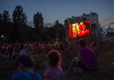 02 agosto 2018-Bucarest, Romania. Persone che aspettano e guardano nel parco pubblico Herastrau l'inizio del film sullo schermo di proiezione del cinema all'aperto