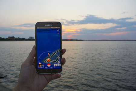 19 August 2018-Bucharest, Romania. Capture of a person playing Pokemon Go on his Samsung phone and the sunset as scenery Editorial