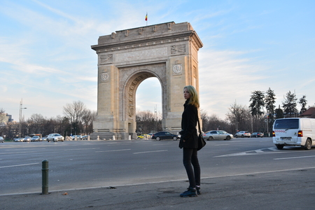 A blonde model with mermaid hair looking at the Arc of Triumph in Bucharest, Romania