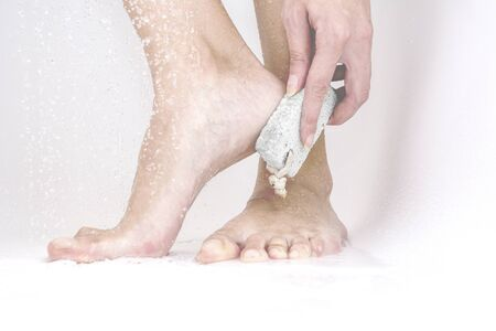 woman scrubbing with pumice to remove the dead skin from the feet 版權商用圖片