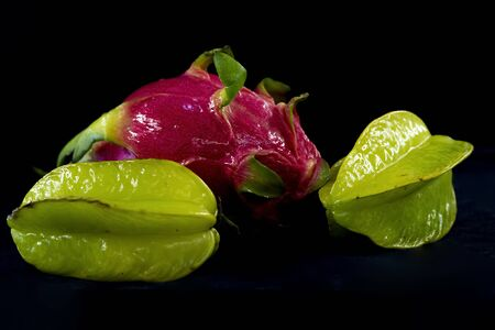 A dragon fruit (pitaya) between two carambola also known as the star fruit