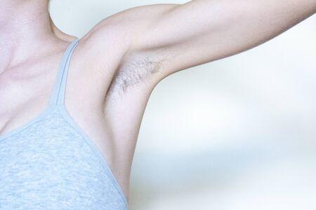 A woman displaying a hairy armpit before shaving it 版權商用圖片