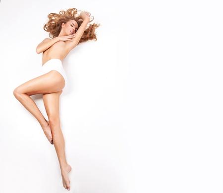 salud sexual: Mujer rubia delicada se extiende sobre un fondo blanco