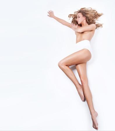 expresion corporal: Mujer rubia delicado que miente en un fondo blanco