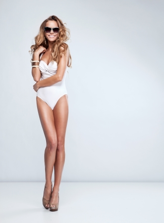 long sexy legs: Sexy woman in swimsuit with sunglasses Stock Photo