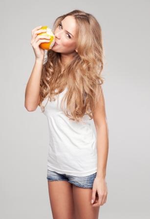 Retrato de uma jovem mulher bonita com laranja