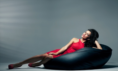 happy rich woman: Sexy brunette woman lies on the black pillow Stock Photo